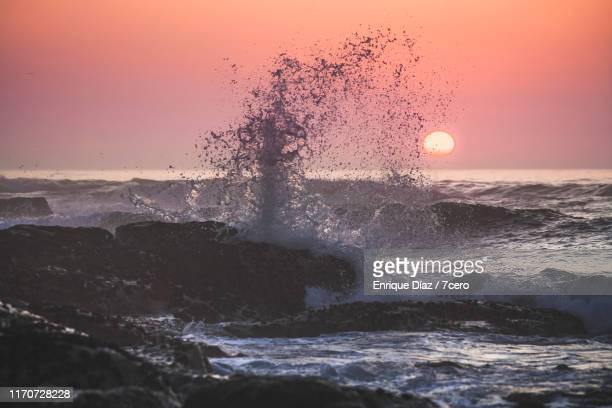 sunset over the ocean with crashing waves, vila praia de âncora, portugal - rebentação imagens e fotografias de stock