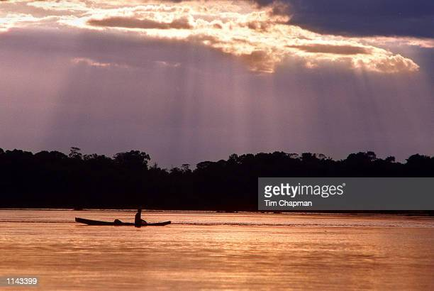 """Sunset over the Orinoco River in the Amazon region of Venezuela December 13, 1998. An Indian paddles his""""bongo"""" home after a day of fishing near the..."""