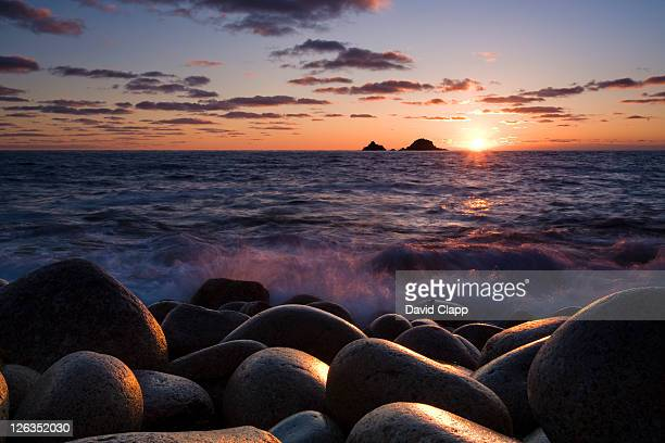 sunset over the pebble shore at porth nanven in cornwall. - pebble stock pictures, royalty-free photos & images