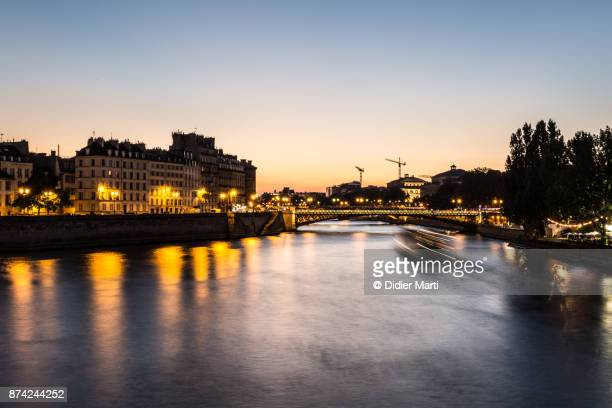 sunset over the seine riverbank in the heart of paris - didier marti stock photos and pictures