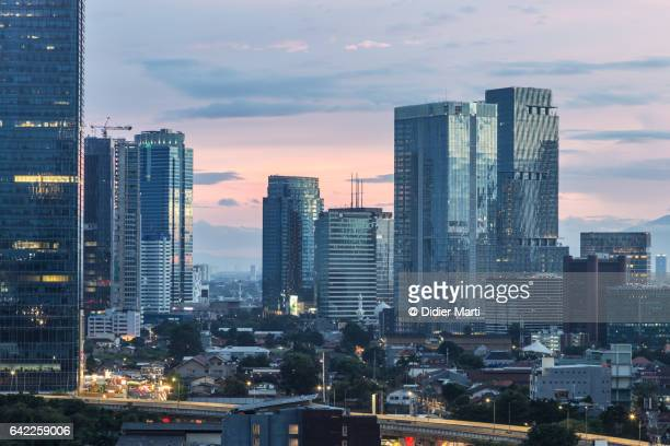sunset over the skyscrapers of the jakarta business district in indonesia capital city - emerging markets stock photos and pictures