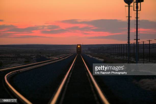sunset over train on tracks in rural landscape - approaching stock pictures, royalty-free photos & images