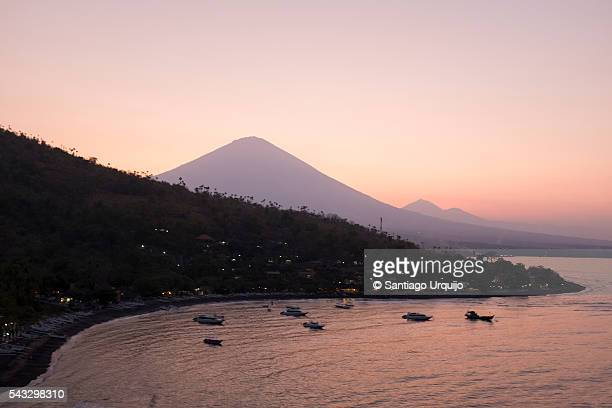 Sunset over village of Amed with volcano Agung on background