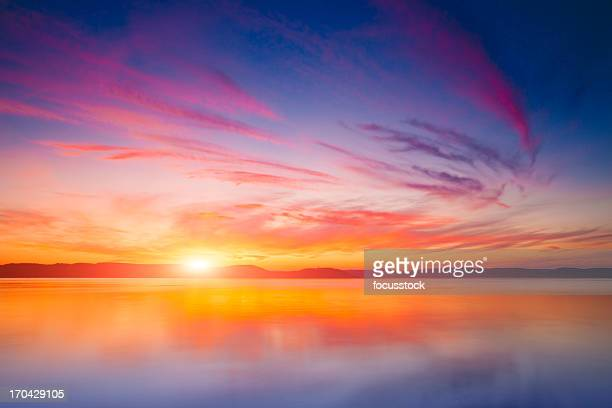 sunset over water - sunset lake stock photos and pictures