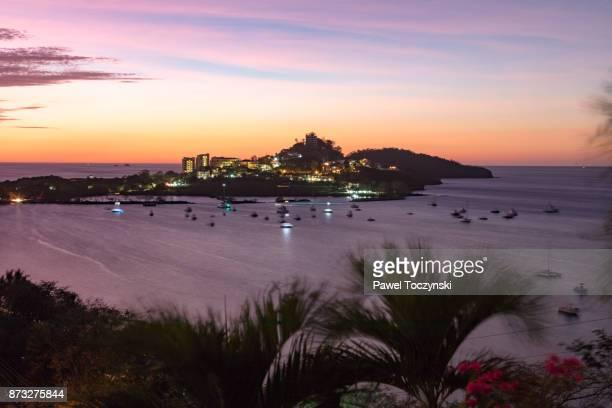sunset overlooking a peninsula dividing playa flamingo and playa portero in playa conchal in the northern part of nicoya peninsula, costa rica - península de nicoya fotografías e imágenes de stock