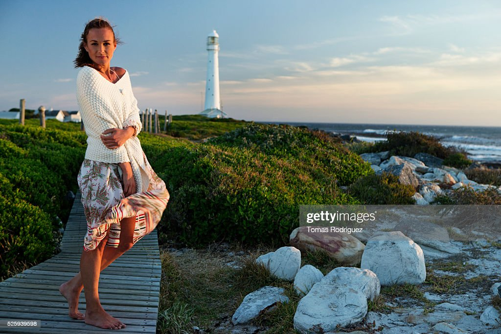 Sunset portrait of young woman standing on jetty : Stock Photo