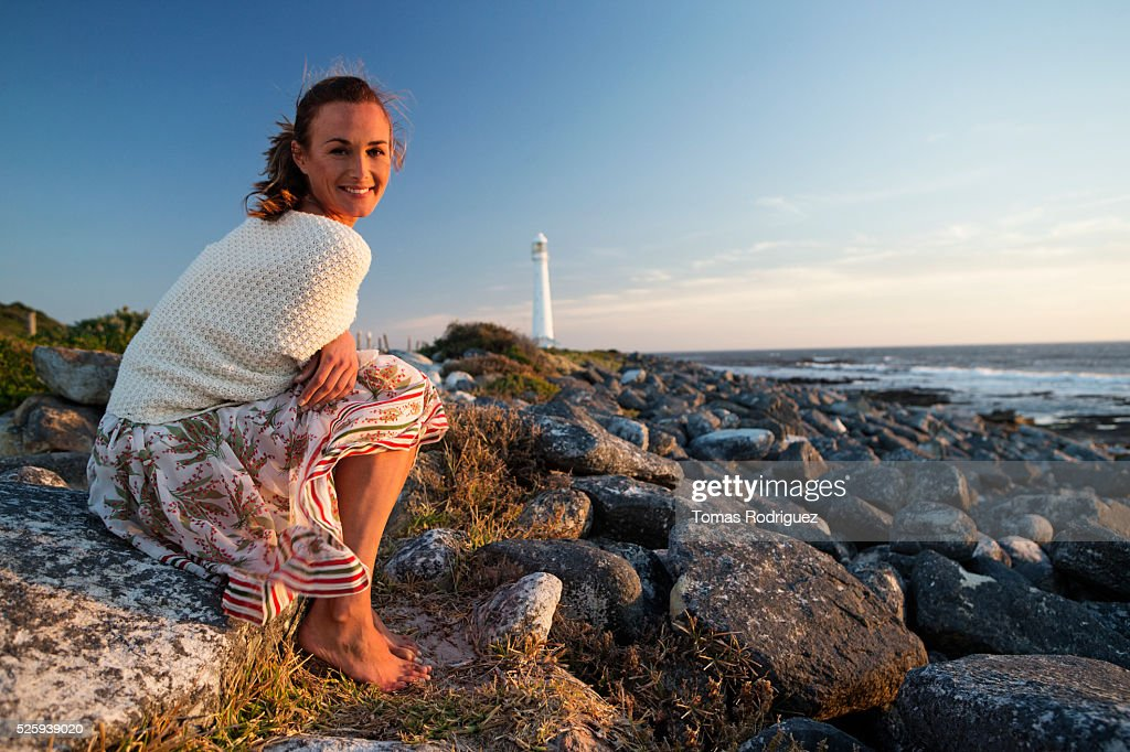 Sunset portrait of young woman with lighthouse in background : Stockfoto