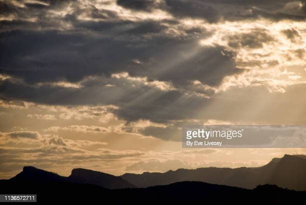 sunset rays over mountain peaks - generic location stock pictures, royalty-free photos & images