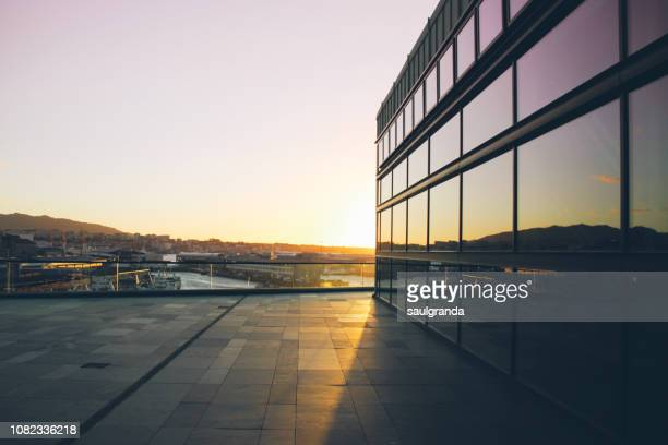 sunset reflected on a glass facade - pontevedra province stock photos and pictures