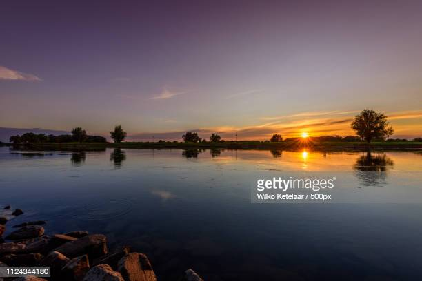 sunset reflections - zonsondergang stock pictures, royalty-free photos & images