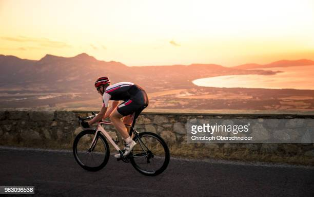 sunset road biking in corsica, france - road cycling stock pictures, royalty-free photos & images