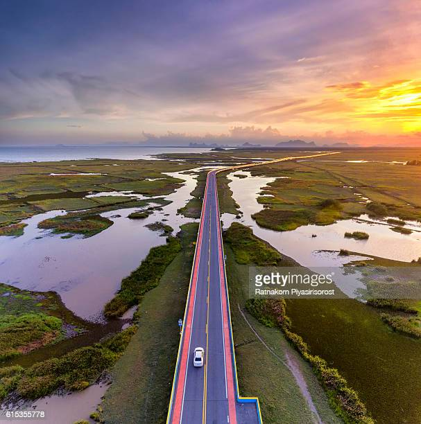sunset scence of aerial view over the road - rushing the field stock pictures, royalty-free photos & images