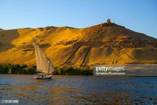 sunset scene of boats on the nile river, aswan - ナイル川 ストックフォトと画像