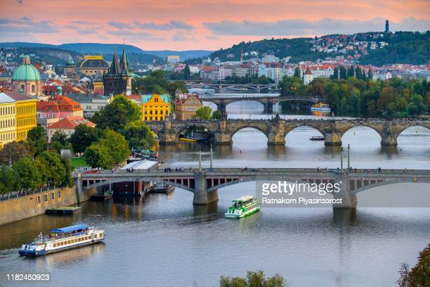 sunset scene of prague old town and charles bridge reflected in vltava river. prague, czech republic - eastern european stock pictures, royalty-free photos & images