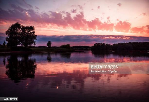 sunset scene over a still lake - milton keynes stock pictures, royalty-free photos & images
