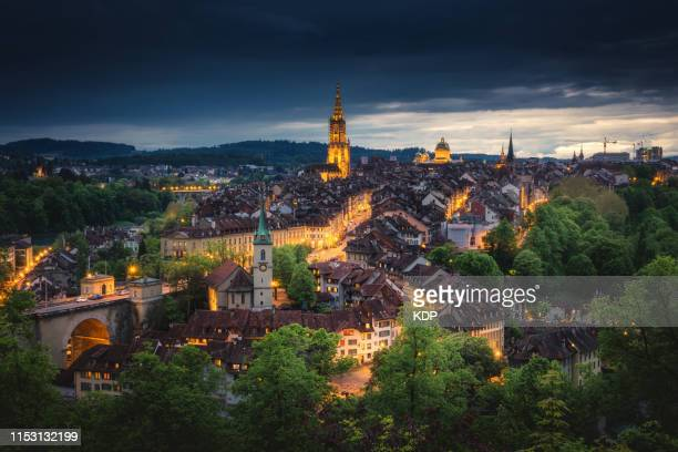 sunset scenery in bern and city illuminating lights, bern, switzerland - bern stock pictures, royalty-free photos & images