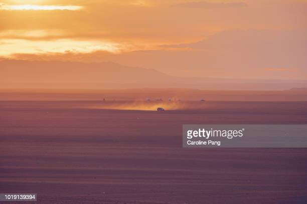 Sunset scenery of an off-road vehicle in high-speed stirs up dust trail on the Gobi desert.