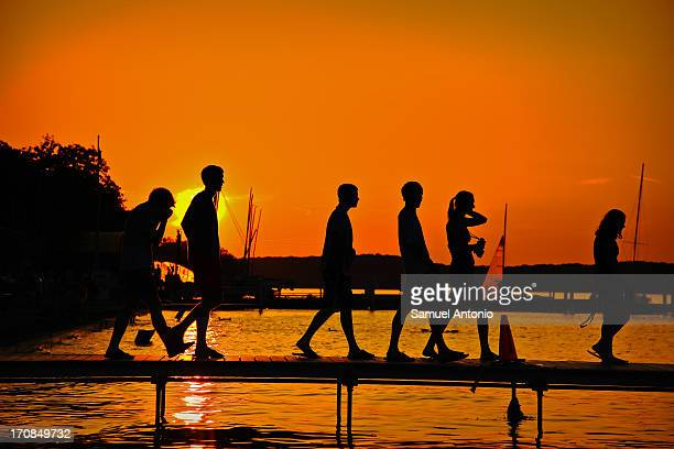 CONTENT] Sunset silhouette of college students on Lake Mendota at the Student Memorial Union Terrace at the University of WisconsinMadison Madison...