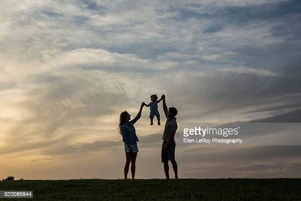 sunset silhouette of young family lifting one-year-old child into the air - atlantic beach north carolina stock pictures, royalty-free photos & images
