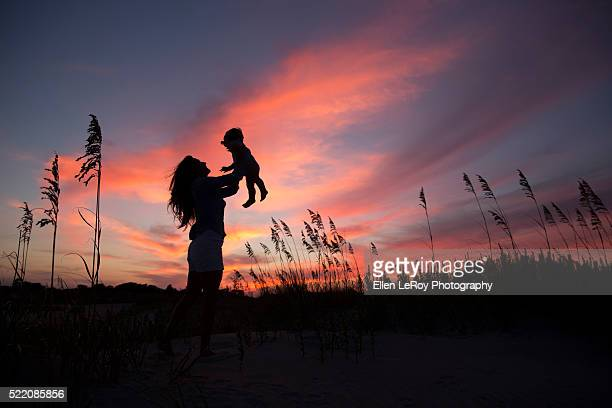 sunset silhouette of young mother lifting one-year-old child into the air on the beach - atlantic beach north carolina stock pictures, royalty-free photos & images