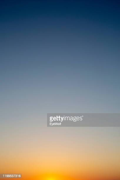 sunset sky color gradient from orange to dark blue - imbrunire foto e immagini stock