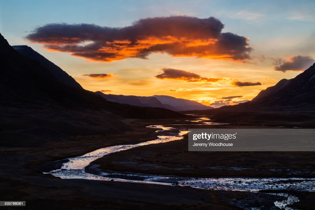 Sunset sky over river and remote mountain landscape : Foto stock