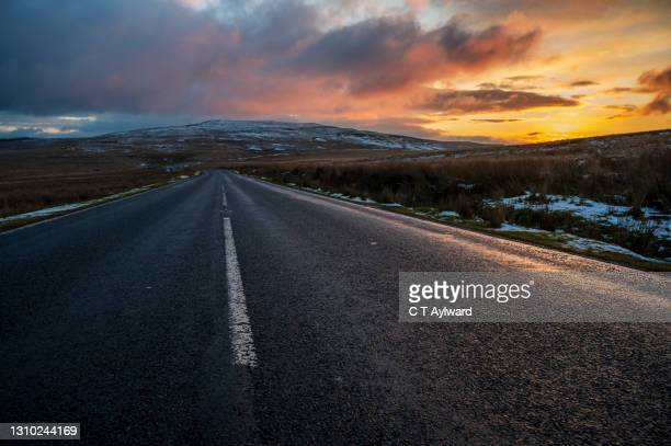 sunset sky, snow and road - sunset stock pictures, royalty-free photos & images