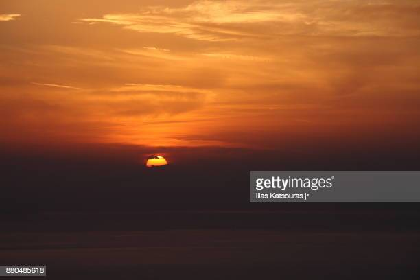 Sunset sky with sun disk hidden behind low clouds