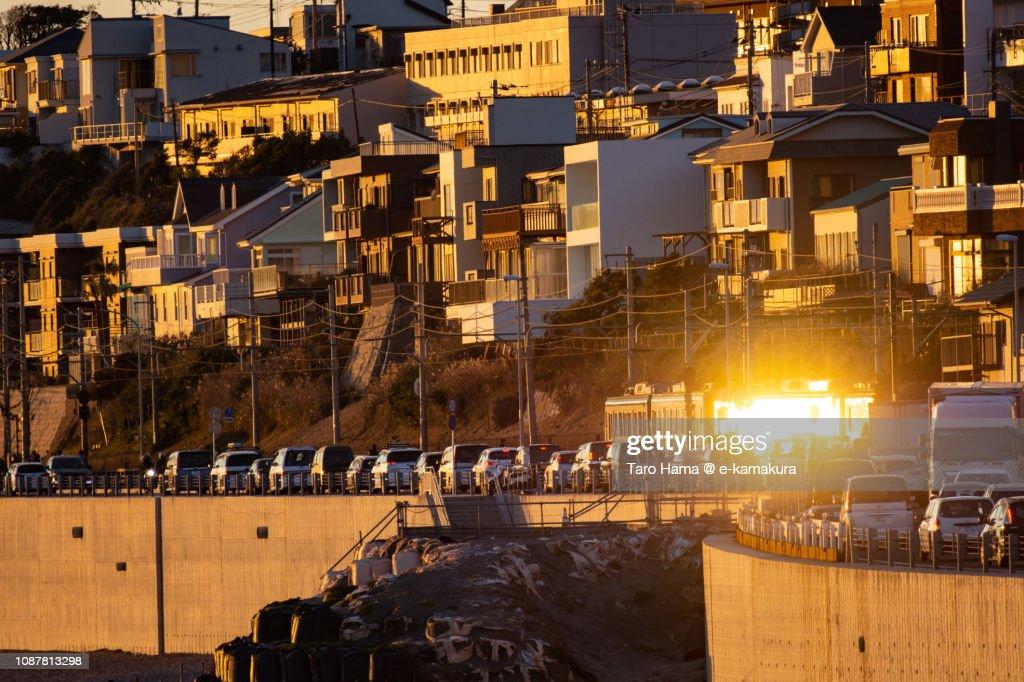 Sunset sunbeam-reflected Enoshima Electric Railway, local train running on the coastline in Kamakura city in Japan : Stock Photo