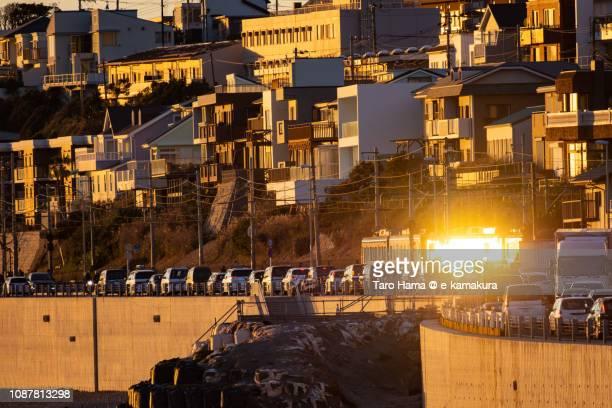 Sunset sunbeam-reflected Enoshima Electric Railway, local train running on the coastline in Kamakura city in Japan
