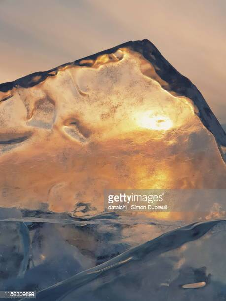 sunset through the pure ice of lake baikal in winter - the four elements stock pictures, royalty-free photos & images