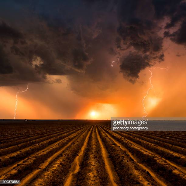 sunset thunderstorm over a ploughed field, nebraska. usa - great plains stock pictures, royalty-free photos & images