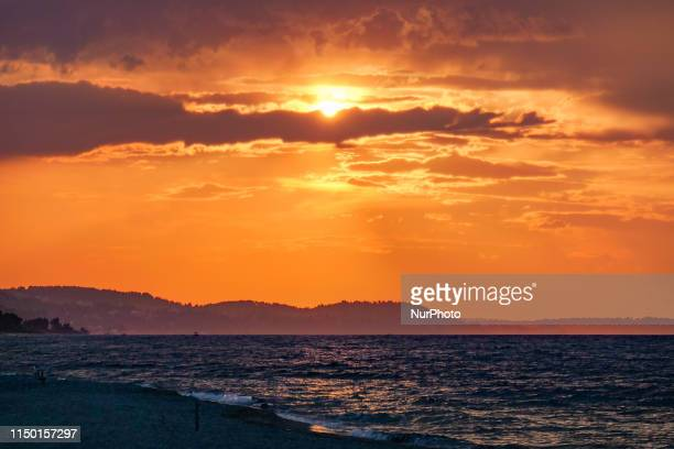 Sunset time with clouds and warm colors at the beach during the summer in Pefkochori, Halkidiki in Northern Greece. Pefkohori and Chalkidiki are a...