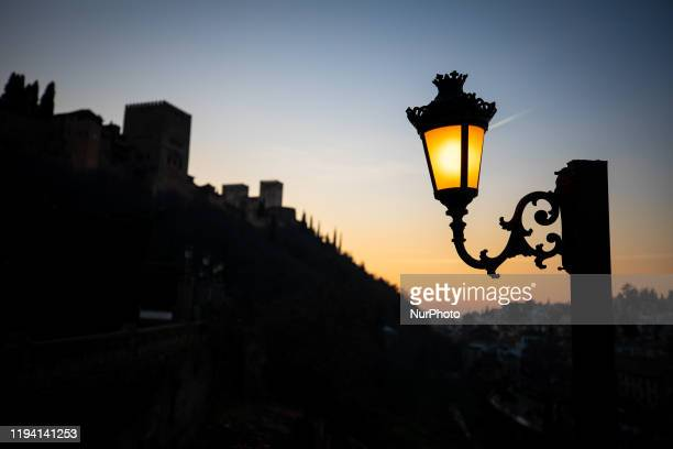 Sunset view of a streetlight with the Alhambra monument in backlight on January 9 2020 in Granada Spain