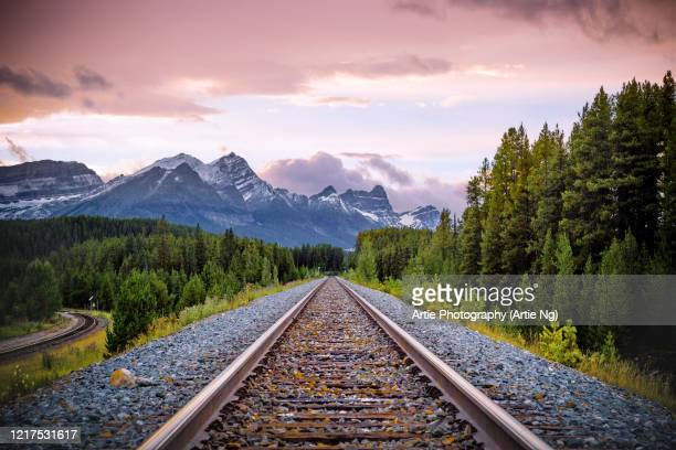 sunset view of canadian rockies and railway track at lake louise, alberta, canada - canadian rockies stock pictures, royalty-free photos & images