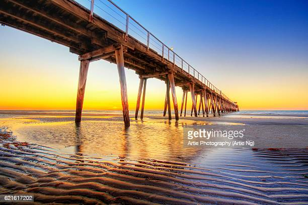 sunset view of largs bay jetty on the lefevre peninsula in the west of adelaide, south australia - adelaide stock pictures, royalty-free photos & images