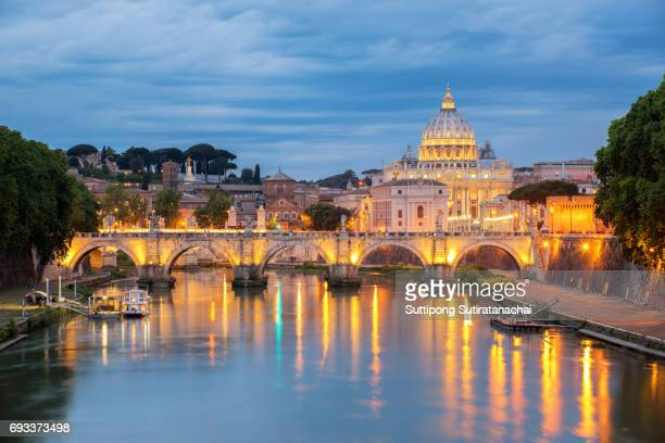 sunset view of st. peters basilica in the vatican and the ponte sant'angelo, bridge of angels, at the castel sant'angelo and river tiber in rome, italy - rome italy stock pictures, royalty-free photos & images