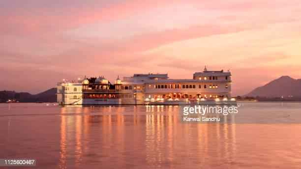 sunset view of taj lake palace floating on lake pichola - palace stock pictures, royalty-free photos & images