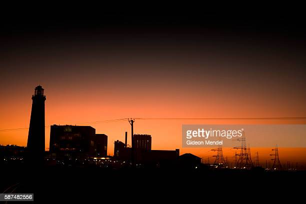 A sunset view of the Dungeness B nuclear power station with a silhouette of the Old Dungeness Lighthouse on the left This is an gascooled reactor...
