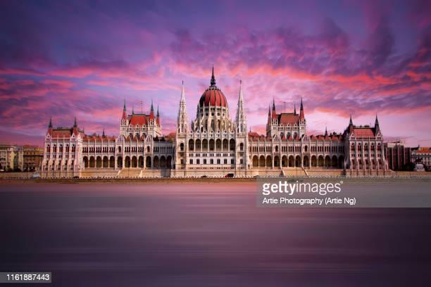sunset view of the hungarian parliament building along river danube, budapest, hungary - sede do parlamento húngaro - fotografias e filmes do acervo