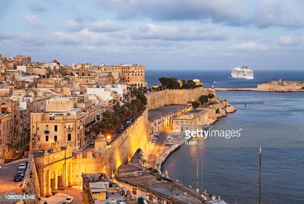 sunset view of valletta old town from upper barrakka gardens, malta - valletta stock pictures, royalty-free photos & images