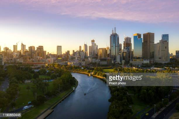 sunset view of yarra river and melbourne skyscrapers business office building with evening skyline in victoria, australia. australia tourism, modern city life, or business finance and economy concept - melbourne austrália - fotografias e filmes do acervo
