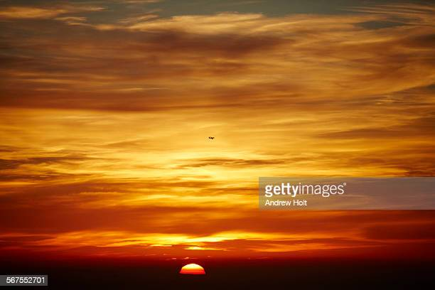 A Sunset with a red sky with a plane and clouds