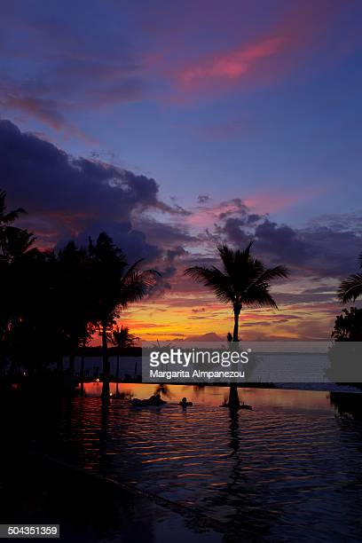CONTENT] Sunset with beautiful red yellow purple and blue colors of the sky over the pool of Oberoi Lombok Resort Indonesia