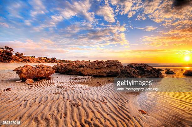 sunset with big rocks and sand patterns at the beach - südaustralien stock-fotos und bilder