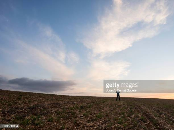 Sunset with clouds of orange color on a ploughed field the spring , with the silhouette of a person contemplating the sky in the distance