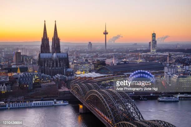 sunset with cologne cathedral and hohenzollern bridge, cologne, north rhine-westphalia, germany - köln stock-fotos und bilder