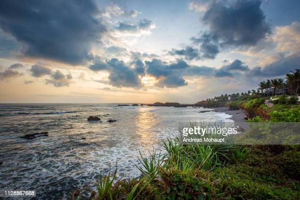 sunset with dramatic clouds over beach in bali, indonesia. - landschaft stock pictures, royalty-free photos & images