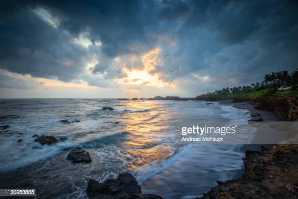 sunset with dramatic clouds over beach in bali, indonesia. - küstenlandschaft stock pictures, royalty-free photos & images