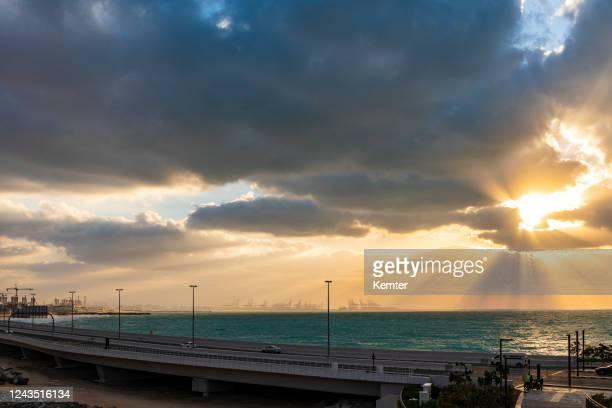 sonnenuntergang mit dramatischem himmel in dubai - kemter stock-fotos und bilder